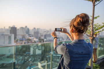 Woman taking a photo of Bangkok skyline in dusk