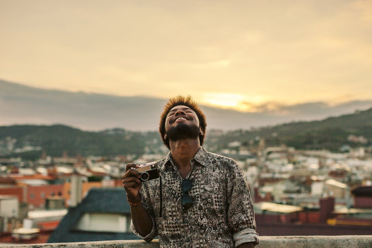 Young black man laughing holding an old camera on a rooftop at sunset.