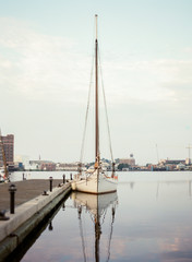 Sailboat docked on calm morning waters
