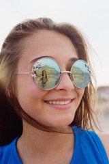Smiling teen wearing sunglasses reflects friend