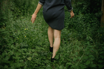 Woman in short dress and ankle boots walking in overgrown alleyway garden