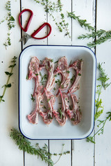 Lamb chops with rosemary and thyme in a baking dish on white wooden background