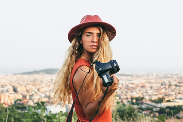 Woman holding a camera to take a photo of the cityscape.