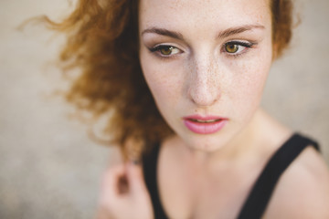 Portrait of a beautiful young woman with freckles and ginger hair