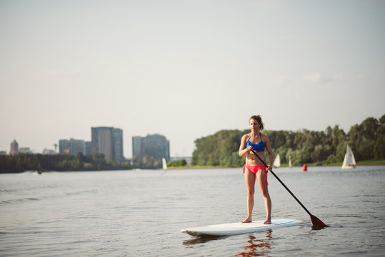 Young fit woman practicing her stand up paddle board skills.
