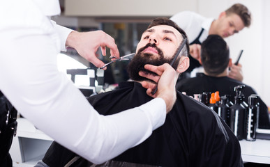 Cheerful man forming beard of client into shape