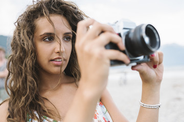 Young woman using an old film camera