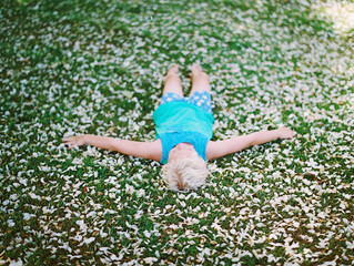 little boy in blue tank top and pjs and laying on bed of flower petals on green grass
