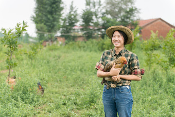 Female farmer holding chicken
