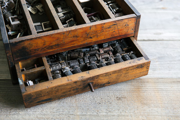 Old wood drawer filled with vintage metal numbering inserts for printer