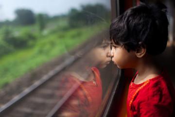 Little girl looking through the train window in a contemplative mood