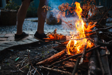 A caucasian man tending to a campfire outdoors in the evening.