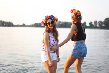 Two beautiful female friends having a good time by the river