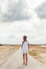 Little girl in a white dress walking on a long road in an open field