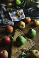Apples and pears scattered over a table.