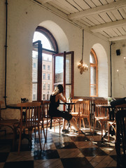 Back view of the woman sitting at a cafe