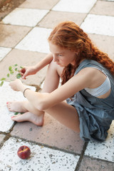 Red hair young girl sitting on the ground in a relaxed moment