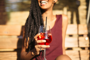 African woman having a drink outdoors