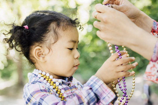 Mother's hands, puting beads necklace on a girl