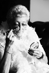 Senior woman putting face powder to her face