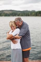 Fun, mature couple hugging together on dock at the lake