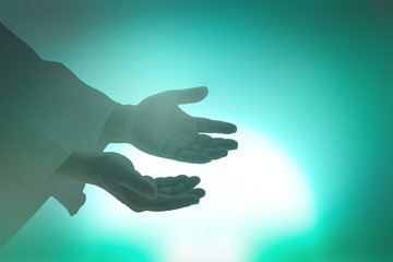 Ascension day concept: Silhouette christian open spiritual hands with palms up over blurred new day background
