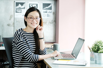 Young businesswoman wearing eyeglasses with smiling face, happy emotion, working at office table, business casual lifestyle