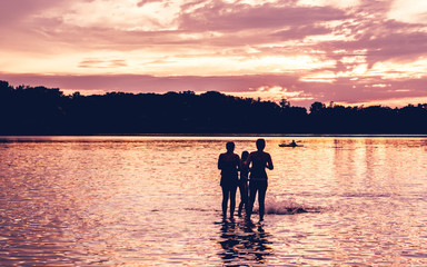 People are having fun at a lake under sunset