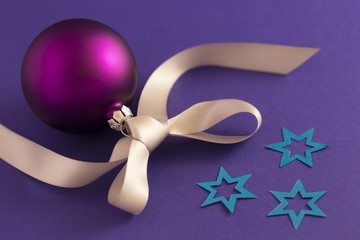 Beautiful purple christmas ball with satin effect, grey gift ribbon and metallic blue stars on purple background.