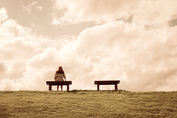 a women sitting alone on a bench waiting for love, alone concept