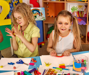 Plasticine modeling clay in children class. kids together play dough and mold from plasticine in kindergarten or preschool. Group of four people. Teaching modeling. Zoo from plasticine.