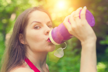 Young woman drinks water after exercising
