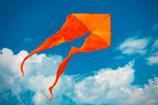 Orange kite in the blue sky with white clouds