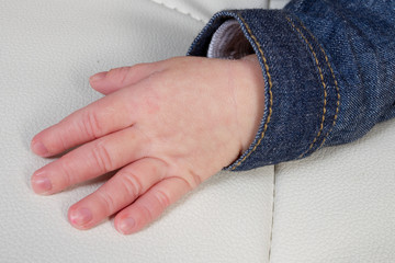 little hand of a new baby newborn with a denim jacket