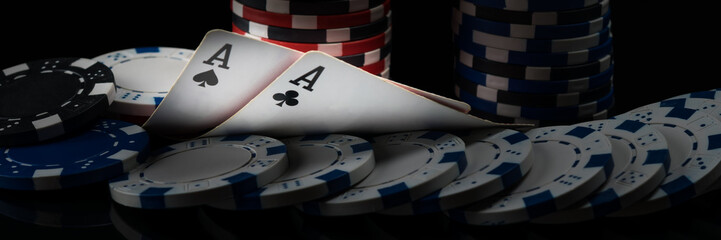 Two black aces on poker cards glow in a dark casino