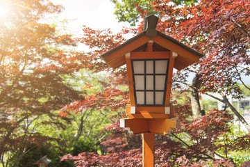 Lamp in japanese style at shrine or temple with autumn leaves background.
