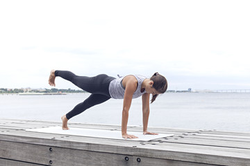 Woman standing in yoga one legged plank by the sea