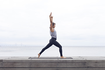 Woman doing yoga sun salutation by the sea
