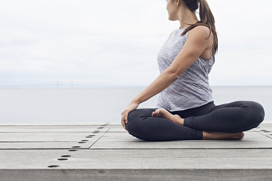 Woman seated in a lotus yoga pose with a twist by the sea