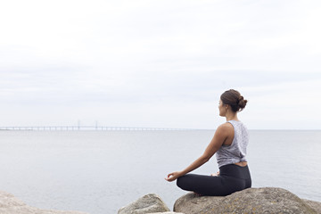 Woman seated in a lotus yoga pose on rocks beside a bay
