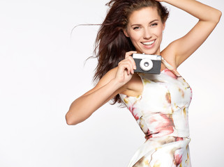 Beautiful and cheerful women modell poses with old camera