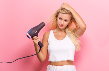 Beautiful woman holding a hairdryer on a pink background