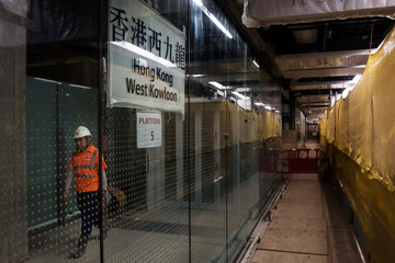 A worker walks past signage for platform 5 of the West Kowloon Terminus of the Guangzhou-Shenzhen-Hong Kong Express Rail Link (XRL) as it stands under construction in Hong Kong