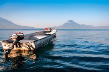 Small boat in the blue waters of Lake Atitlan in Guatemala with volcanoes in the background