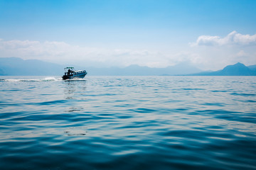 A boat going into the mist at lake Atitlan in Guatemala