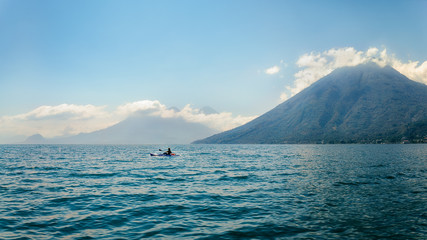 A Kayaker in the blue waters of Lake Atitlan in Guatemala, on a misty morning in front of volcano San Pedro. Further away in the mist we can see Volcanos Toliman and Atitlan.