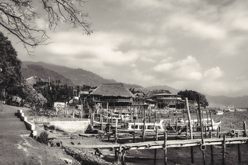 The small village of Panajachel on the shore of Lake Atitlan in Guatemala in black and white. Tourist boats at the docks are used for the tour of the lake.