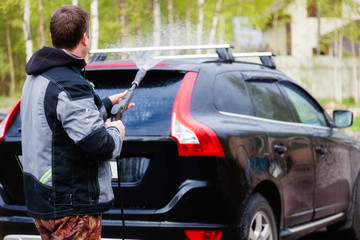 A man washes his car in the yard
