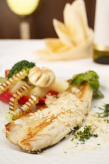 Hake fillet with grilled vegetables arranged on a plate, Traditional dish in elegant setting, Selective focus with soft light