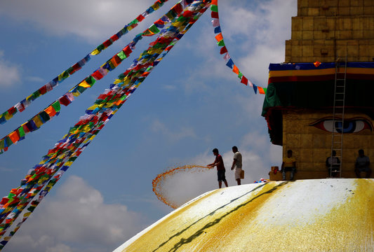 A man splashes paint on the dome of Boudhanath Stupa, a UNESCO world heritage site famous among tourists, in Kathmandu